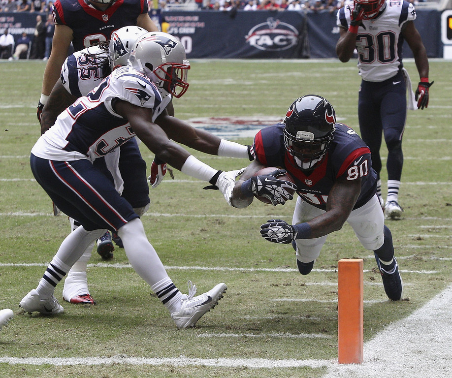 . Andre Johnson #80 of the Houston Texans dives for the pilon as Devin McCourty #32 of the New England Patriots knocks him out of bounds at Reliant Stadium on December 1, 2013 in Houston, Texas.  (Photo by Bob Levey/Getty Images)