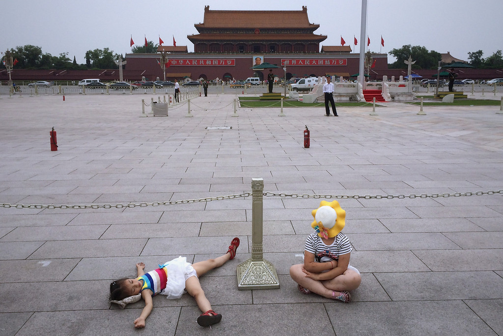 . Two Chinese tourists rest in Tiananmen Square on June 4, 2014 in Beijing, China. Twenty-five years ago on June 4, 1989 Chinese troops cracked down on pro-democracy protesters and in the clashes that followed scores were killed and injured. (Photo by Feng Li/Getty Images)