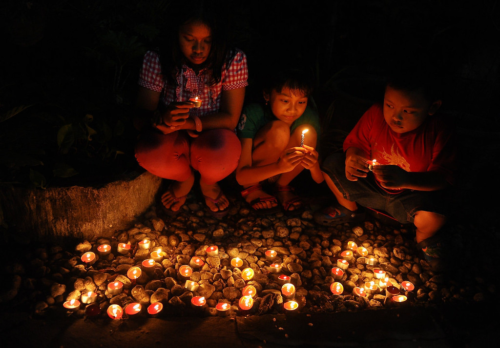 . Young Indonesians light candles and pray to celebrate 2014 New Years on December 31, 2013 in Surabaya, Indonesia. A wave of pyrotechnic displays kicked off New Years celebrations in major cities around the world.  (Photo by Robertus Pudyanto/Getty Images)
