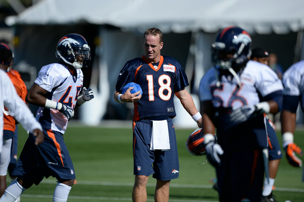. Denver Broncos quarterback Peyton Manning (18) heads to stretching as he carries a football in a blue cover during the start of the Denver Broncos 2014 training camp July 24, 2014 at Dove Valley. (Photo by John Leyba/The Denver Post)