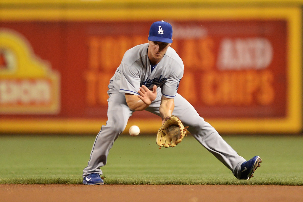 . CINCINNATI, OH - SEPTEMBER 8:  Mark Ellis #14 of the Los Angeles Dodgers fields a ground ball hit by Joey Votto #19 of the Cincinnati Reds in the first inning at Great American Ball Park on September 8, 2013 in Cincinnati, Ohio. Ellis threw Votto out.  (Photo by Jamie Sabau/Getty Images)