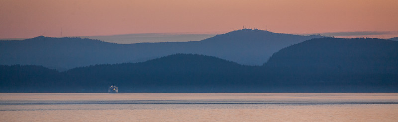 The sunset colors layers of hills and a British Columbia ferryboat - , Capital, British Columbia, Canada (CA)