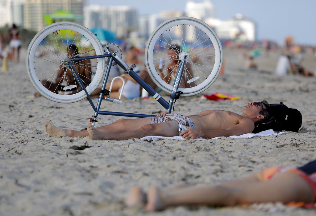 . Chris Borchetta, of Miami Beach, Fla., takes advantage of a sunny day as he lies on the beach, Wednesday, Dec. 14, 2016, in Miami Beach, Fla. Temperatures are above average and in the mid-80\'s in South Florida as an arctic cold front moves from the Plains to the Ohio and Tennessee Valleys, and towards the mid-Atlantic and Northeast by Thursday. (AP Photo/Lynne Sladky)