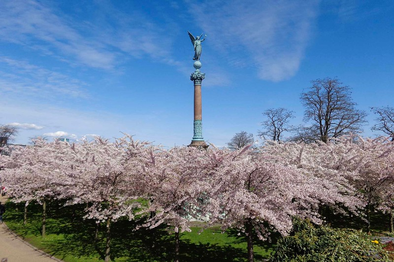 statue on pedestral surrounded by spring blossoms