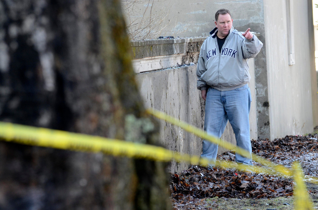 . Sgt Glen Decker investigates the scene of a fatal crash at Pittsfield High School on East Street the day after the accident in search of any debris related to the incident, Wednesday January 15, 2014. The victims were identified as Ernest Duck Jr., 37, of Pittsfield, who is believed to have been the driver of the 2013 Nissan Altima, and passenger Tariq Salley, 34, of Pittsfield.  (AP Photo Ben Garver, Berkshire Eagle Staff)