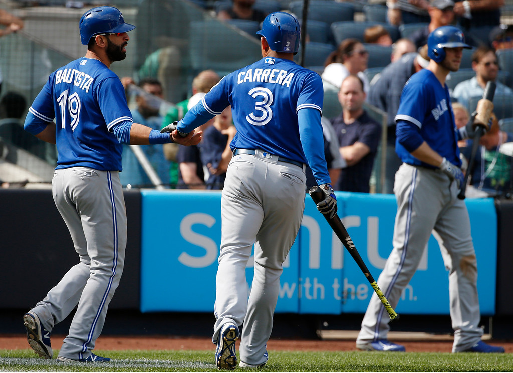 . Toronto Blue Jays\' Jose Bautista (19) and Ezequiel Carrera (3) celebrate after scoring on Edwin Encarnacion\'s two-run single during the seventh inning of a baseball game against the New York Yankees in New York, Monday, Sept. 5, 2016. (AP Photo/Kathy Willens)