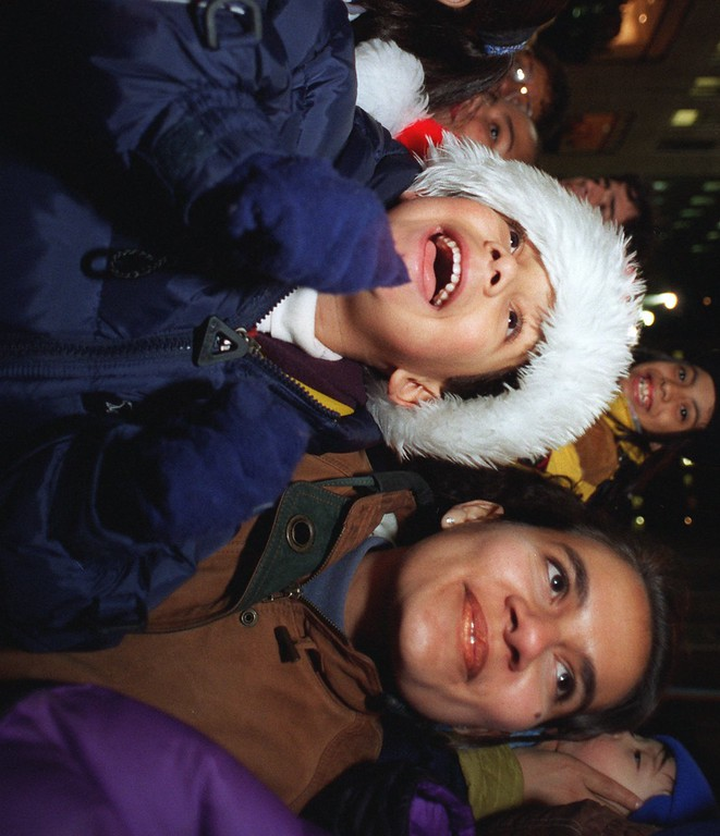 . Giovanne Gotay, 5, accompanied by his mother Nutley Gotay, of Waleska, N.J., smiles the moment the lights flick on  during the 63rd annual lighting of the 75-foot high,  63-year-old, Norway Spruce  in New York\'s Rockefeller Center Tuesday, Dec. 5, 1995. A contingent of  nuns from the Sisters of Christian Charity in Mendham, N.J. - the former owners of the tree - were on hand for the ceremony. (AP Photo/Mitsu Yasukawa)