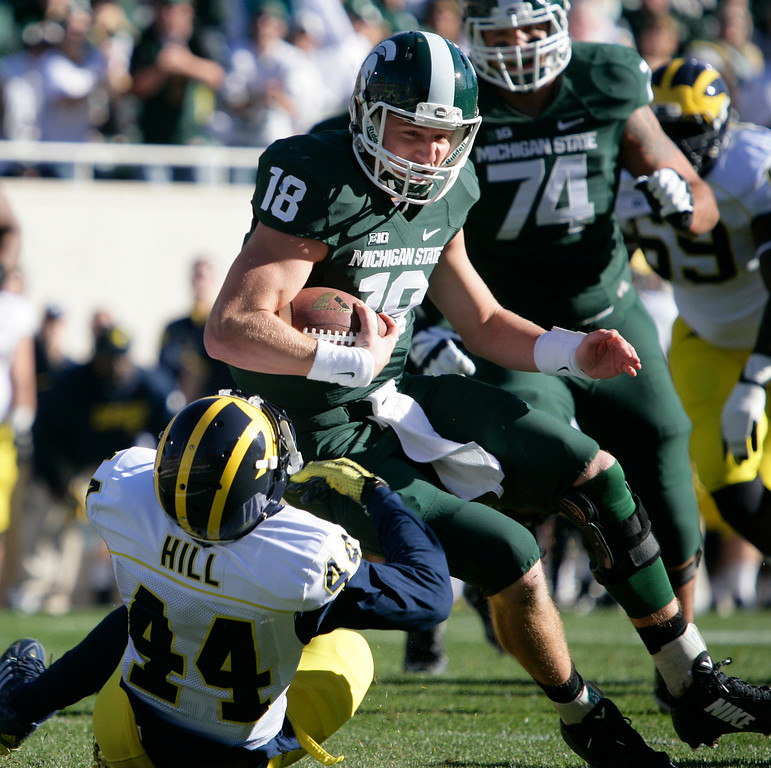 . Michigan State quarterback Connor Cook (18) is tackled on a keeper by Michigan\'s Delano Hill (44) during the first quarter of an NCAA college football game, Saturday, Oct. 25, 2014, in East Lansing, Mich. (AP Photo/Al Goldis)
