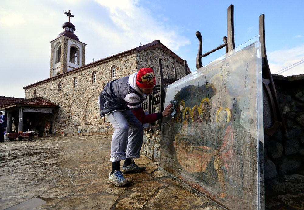 Description of . A man wipes the water from an icon, taken out of a flooded church in the village of Murtino, southeastern Macedonia, Wednesday, Feb. 27, 2013. About 1,000 people had been evacuated due to the floods in eastern Macedonia, after three days of heavy rain. (AP Photo/Boris Grdanoski)