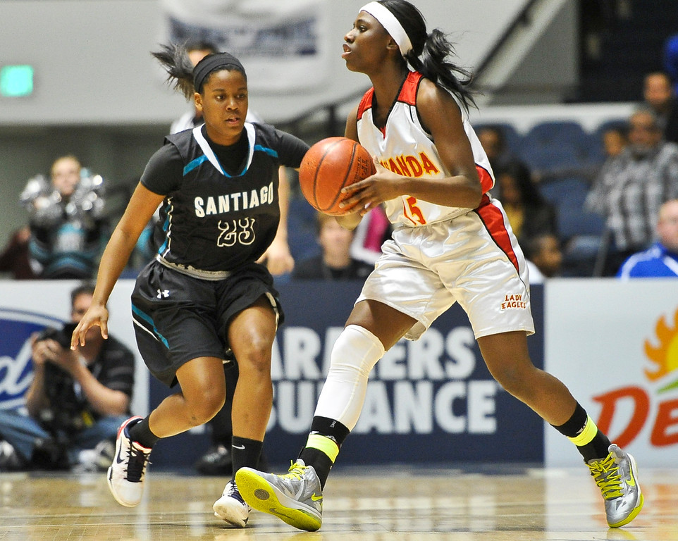 . Etiwanda\'s McKynzie Fort (15) looks for an open pass while being guarded by Santiago\'s Shiana Carrington (23) during the CIF-SS Div. I-AA Girls Basketball Championship game at the Anaheim Convention Center on Friday, Mar. 1, 2013. Etiwanda was defeated by Santiago 70-65. (Rachel Luna / Staff Photographer)