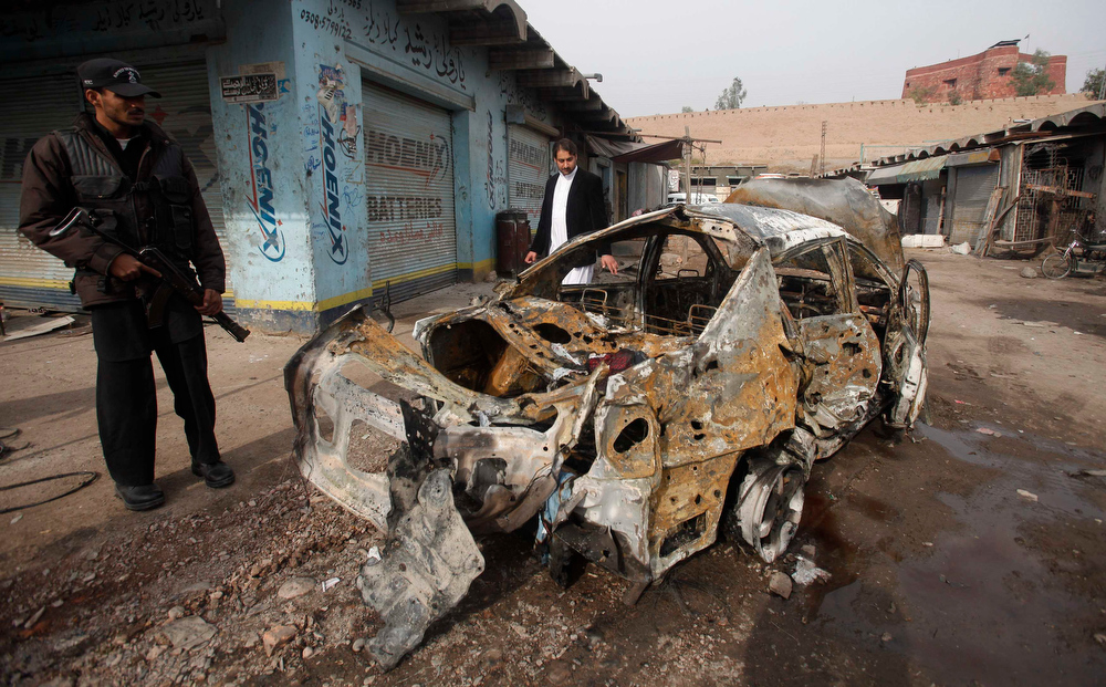 . A police officer stands near a car which was damaged during a bomb attack at Fauji Market in Peshawar December 17, 2012. The blast in the market in northwest Pakistan on Monday killed at least 15 people, a security official said. The official said at least 20 people had been wounded in the blast in the market in the Khyber region, near the border with Afghanistan, and the death toll could rise.   REUTERS/Fayaz Aziz