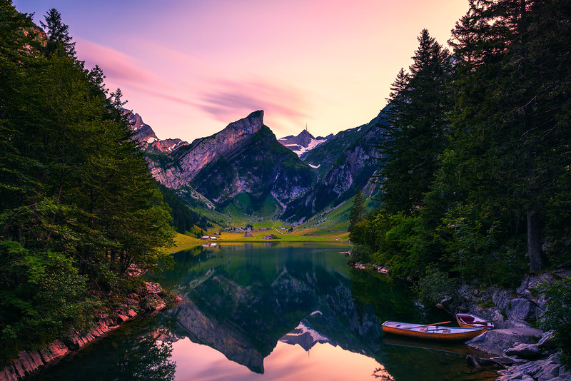 Sunset over the Seealpsee lake with small boats in the Swiss Alps, Switzerland