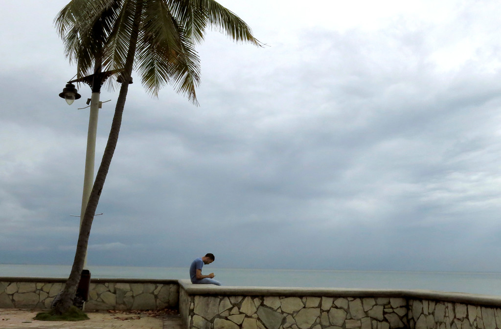 . A man looks at his smartphone along the seafront, in the hours before the arrival of Hurricane Maria, in Santo Domingo, Dominican Republic, Wednesday, Sept. 20, 2017.  (AP Photo/Ezequiel Abiu Lopez)