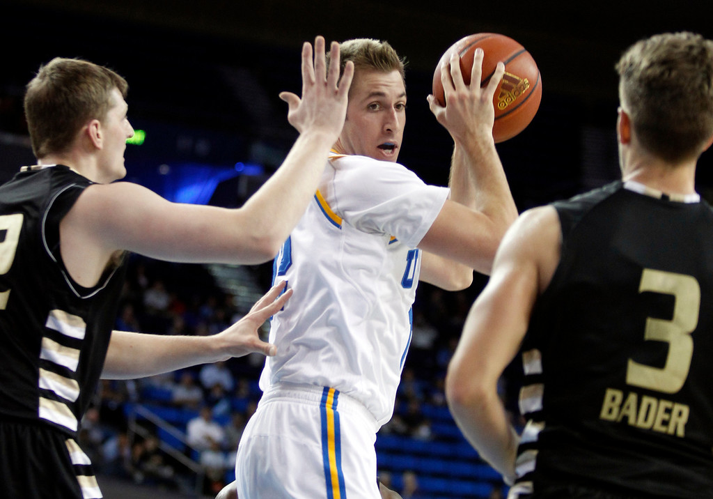 . UCLA forward David Wear, center, pulls down a rebound against Oakland forward Joey Asbury, left, and guard Travis Bader, right, in the second half of an NCAA college basketball game Tuesday, Nov. 12, 2013, in Los Angeles. UCLA won the game 91-60. (AP Photo/Alex Gallardo)