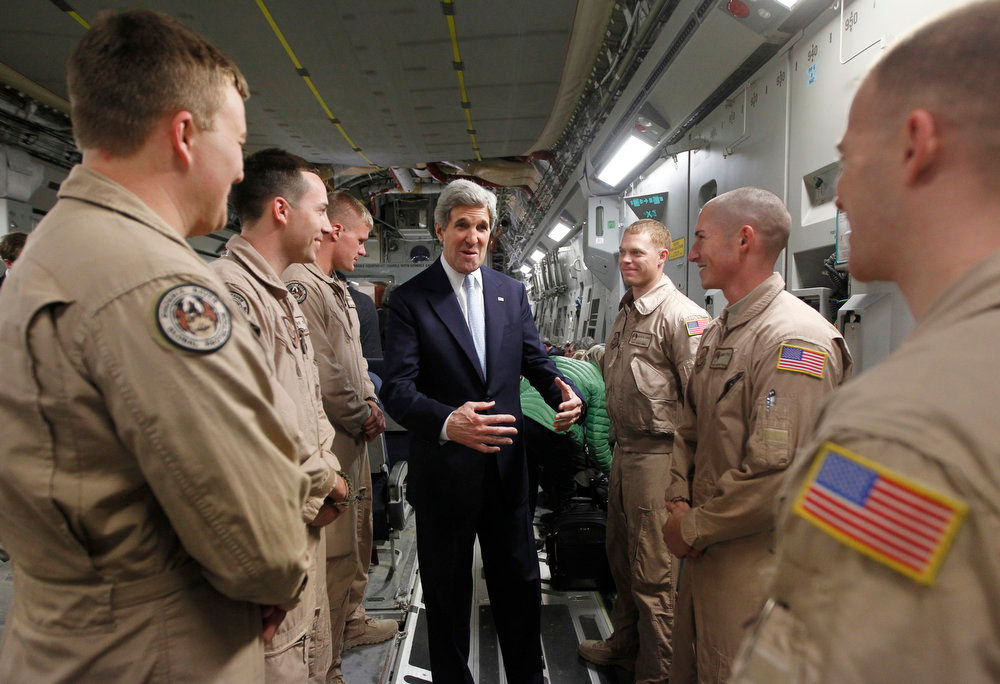 . U.S. Secretary of State John Kerry speaks with members of the U.S. Air Force 816 Expeditionary Airlift Squadron aboard a C-17 aircraft bound for Baghdad on March 24, 2013 in Amman, Jordan. Kerry is expected to urge Iraqi Prime Minister Nuri al-Maliki during his visit to ensure that Iranian flights over Iraq do not carry arms and fighters to Syria. (Photo by Jason Reed - Pool/Getty Images)