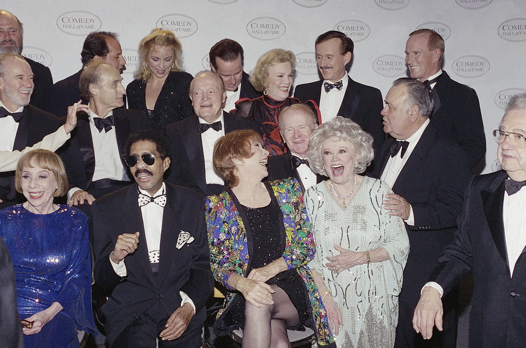 """. Jonathan Winters\', right, middle row, droll humor draws guffaws from comedy greats waiting for a group photo at the taping of NBC\'s second annual \""""Comedy Hall of Fame\"""" shown on Sunday Aug. 29, 1994 in Beverly Hills, California. Left to right, front are Richard Pryor, Shirley Maclaine and Phyllis Diller; middle, Sid Caesar, Bob Hope, Nanette Fabray, Red Buttons; rear, Phil Hartman, Dick and Tom Smother. Honored for their lifetime achievement were Hope, Maclaine, and Sid Caesar, Mary Tyler Moore, George Carlin and Richard Pryor. (AP Photo/Reed Saxon)"""