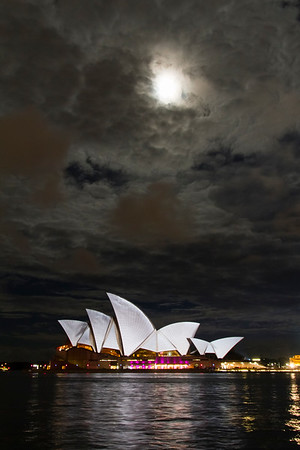 A rare and very lucky shot.  This is the moon over the Opera House and the Opera House itself is lit by special lighting for the annual Vivid Sydney show in which creative and interactive lighting displays were lit up all along the waterfront.