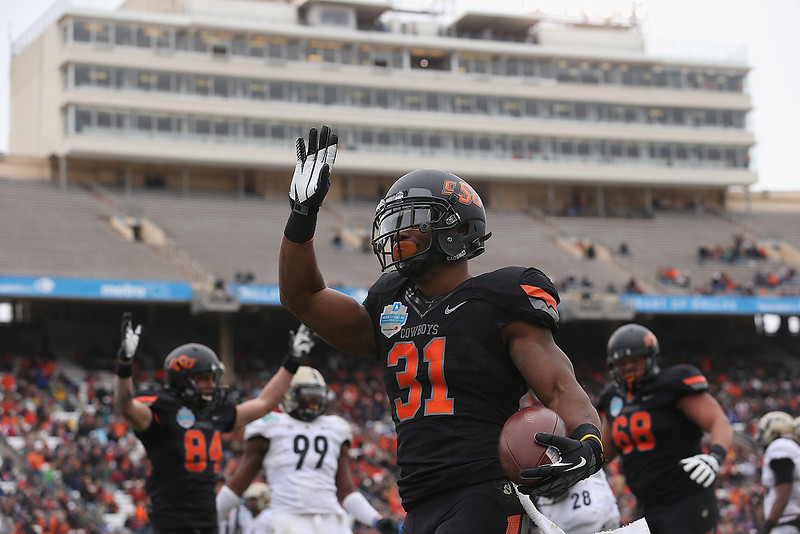 . Jeremy Smith #31 of the Oklahoma State Cowboys celebrates a touchdown against the Purdue Boilermakers during the Heart of Dallas Bowl at Cotton Bowl on January 1, 2013 in Dallas, Texas.  (Photo by Ronald Martinez/Getty Images)