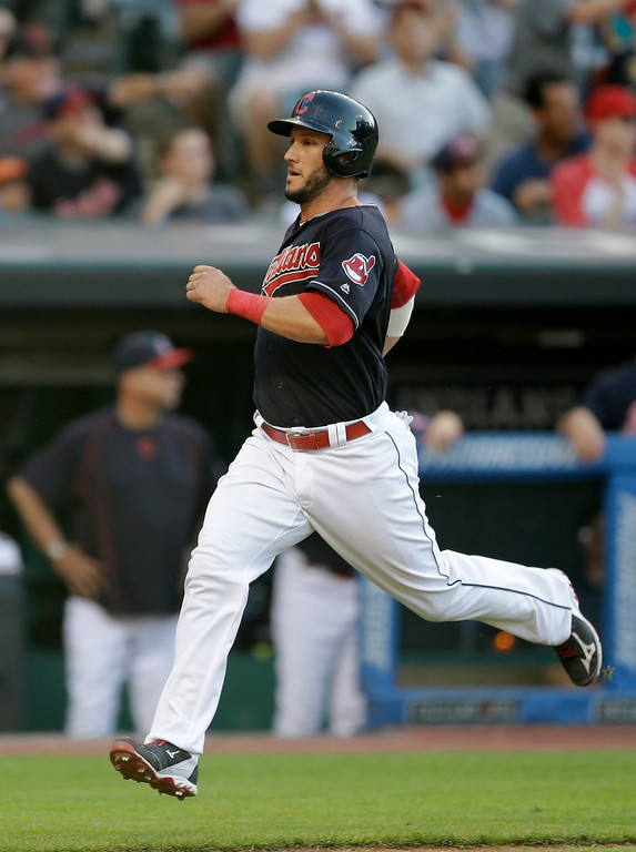 . Cleveland Indians\' Yan Gomes scores on a three-run triple hit by Tyler Naquin in the fourth inning of a baseball game against the Chicago White Sox, Saturday, June 18, 2016, in Cleveland. Juan Uribe and Yan Gomes scored on the play. (AP Photo/Tony Dejak)