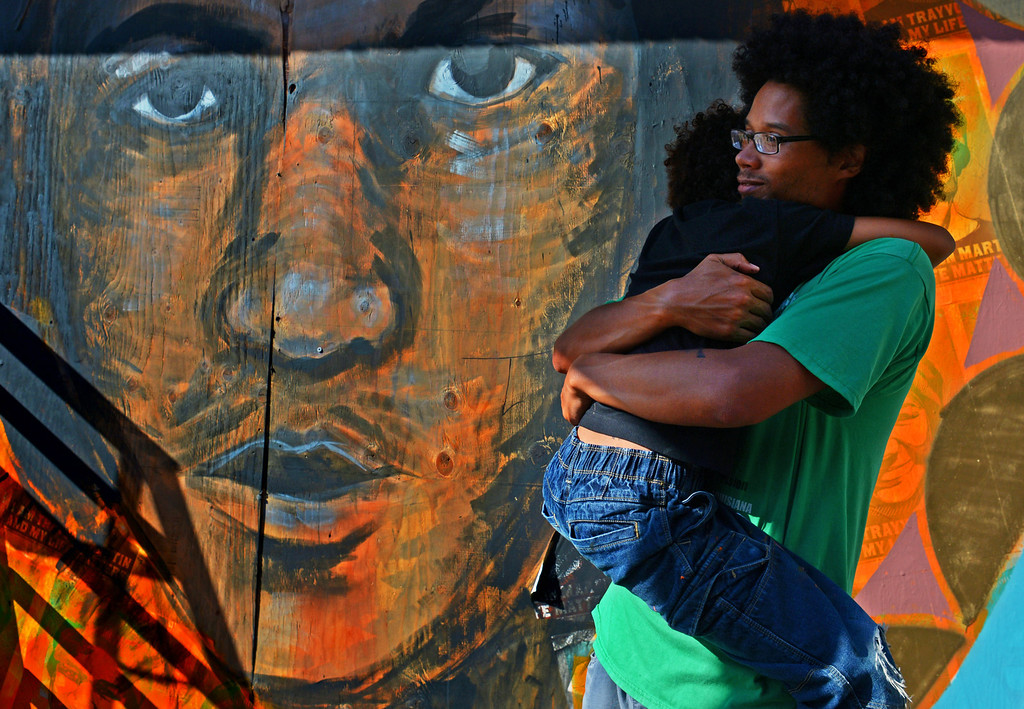 """. Artist Robert Trujillo holds his son Saja Duchicela-Trujillo in front of a mural of Trayvon Martin he is working on at the Youth Radio Building in Oakland, Calif., on Friday, July 19, 2013. Trujillo is with the group \""""Trust Your Struggle,\"""" an artist collective in the Bay Area. The mural is being painted on the wooden boards used to cover the glass windows that were broken during a protest following the acquittal of George Zimmerman in the shooting death of Trayvon Martin. (AP Photo/Bay Area News Group, Jose Carlos Fajardo)"""