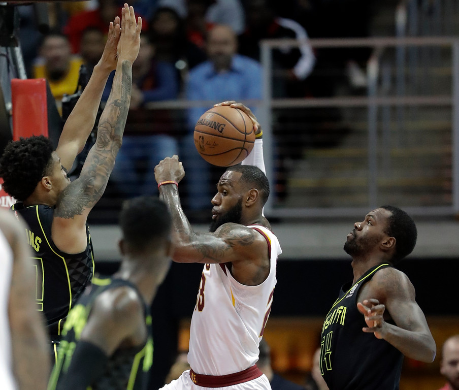 . Cleveland Cavaliers forward LeBron James (23) works against Atlanta Hawks forward John Collins (20) and Atlanta Hawks center Dewayne Dedmon (14) in the first half of an NBA basketball game Friday, Feb. 9, 2018, in Atlanta. (AP Photo/John Bazemore)