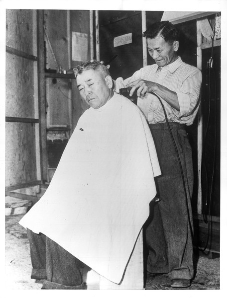 """""""The barbers in Santa Anita Assembly center set up in the street.  Here is one Japanese barber hard at work.""""--caption on photograph"""