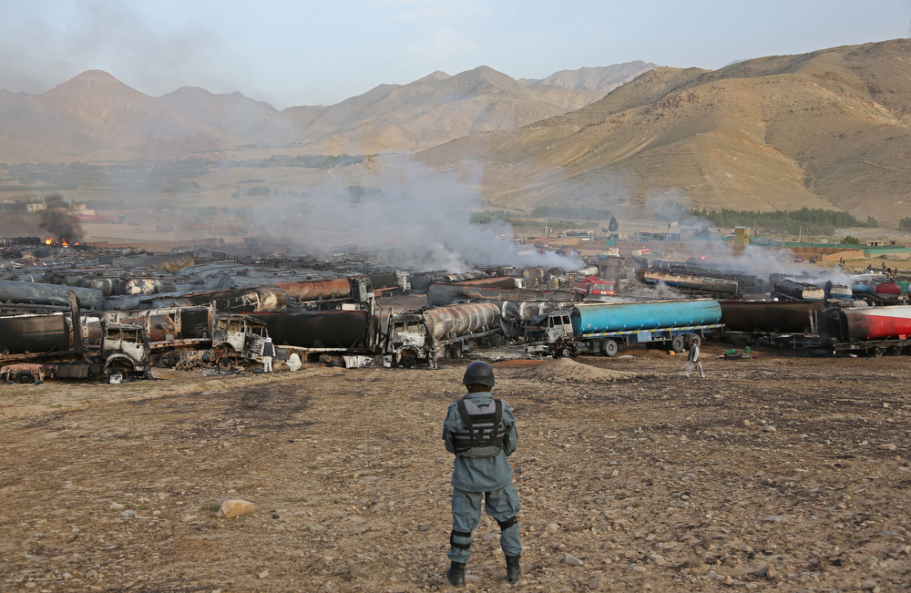 . An Afghan policeman stands guard at the site of burning oil tankers after an attack claimed by Taliban militants on the outskirts of Kabul, Afghanistan, Saturday, July 5, 2014. An Afghan security official says at least 400 fuel tankers caught fire late Friday night in a parking lot in the outskirts of Kabul and there are fears of casualties. (AP Photo/Rahmat Gul)
