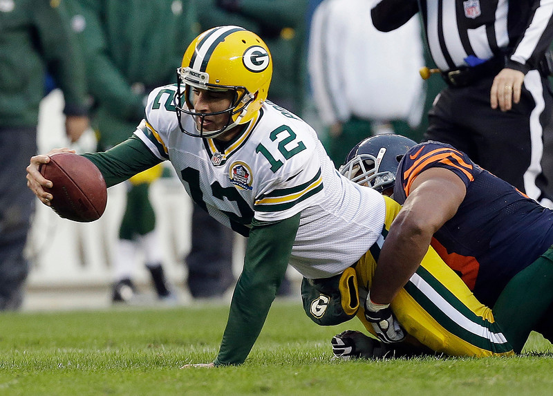 . Green Bay Packers quarterback Aaron Rodgers (12) is tackled by Chicago Bears defensive end Corey Wootton in the second half of an NFL football game in Chicago, Sunday, Dec. 16, 2012. The Packers won 21-13 to clinch the NFC North division title. (AP Photo/Nam Y. Huh)