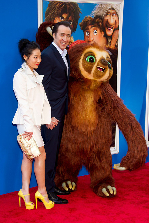 ". Nicolas Cage and his wife, Alice Kim, pose with Belt the sloth at ""The Croods\"" premiere on Sunday, March 10, 2013 in New York. (Photo by Charles Sykes/Invision/AP)"