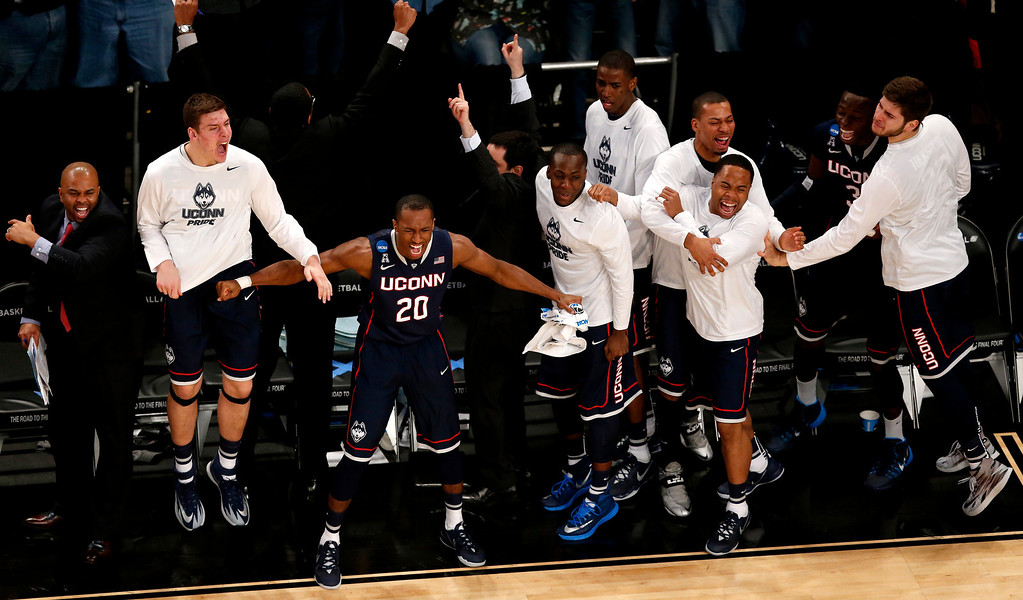 . Connecticut players react during the second half in a regional semifinal at the NCAA college basketball tournament against Michigan State, Sunday, March 30, 2014, in New York. (AP Photo/Julio Cortez)