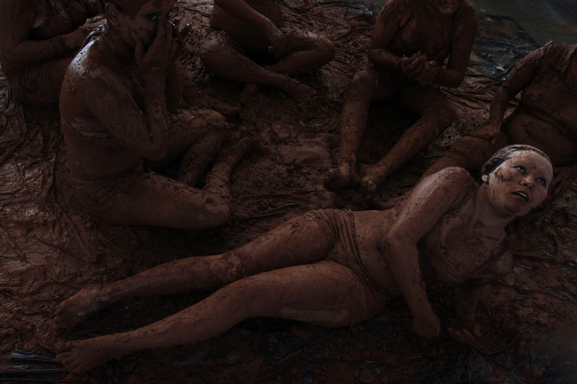 . Women bathe in mud in a presentation for the inauguration of the National Meeting of Rural Women, in Brasilia, Brazil, Monday, Feb. 18, 2013. The four-day event aims to discuss the issues of violence against women and exploitation of women in rural areas. (AP Photo/Eraldo Peres)