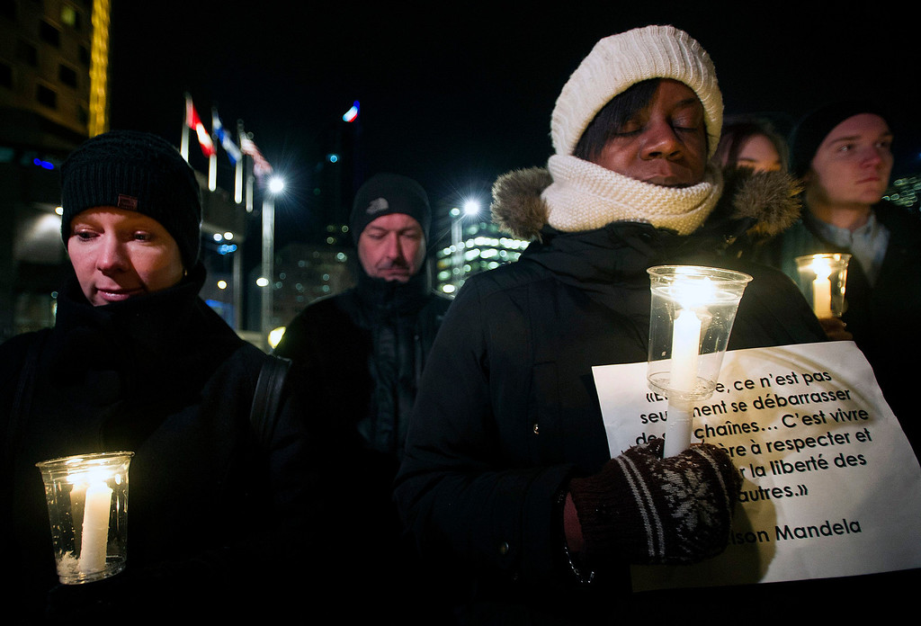 . Members of the public hold candles during a vigil to honor the life and memory of the late Nelson Mandela in Montreal, Friday, Dec. 6, 2013. Mandela died on Thursday at the age of 95. (AP Photo/The Canadian Press, Graham Hughes)