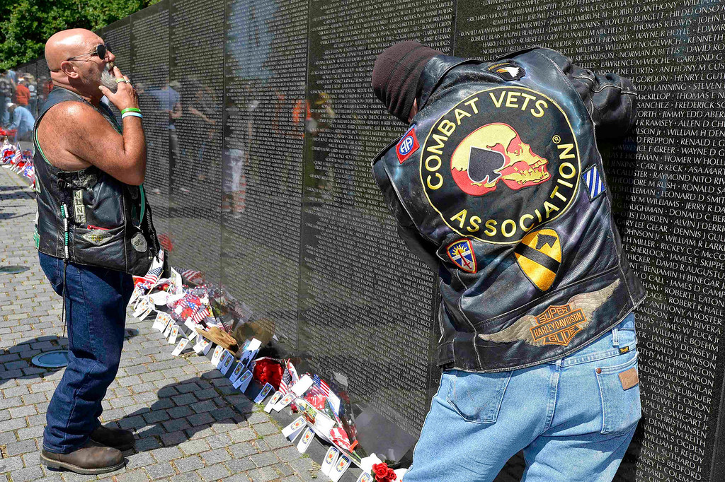 ". ""Trojan\"" Calton of Chillicothe, Ohio (L) searches for the name of a fallen US soldier as Ray Ball, of Newark, Delaware, a U.S. Army reservist with an upcoming deployment to Afghanistan, rubs a name on the Vietnam Veterans Memorial, as they join hundreds of thousands of motorcycle riders on Memorial Day weekend for the 26th Annual Rolling Thunder Rally to remember POWs and MIAs from America\'s wars, in Washington, May 26, 2013.   REUTERS/Mike Theiler"