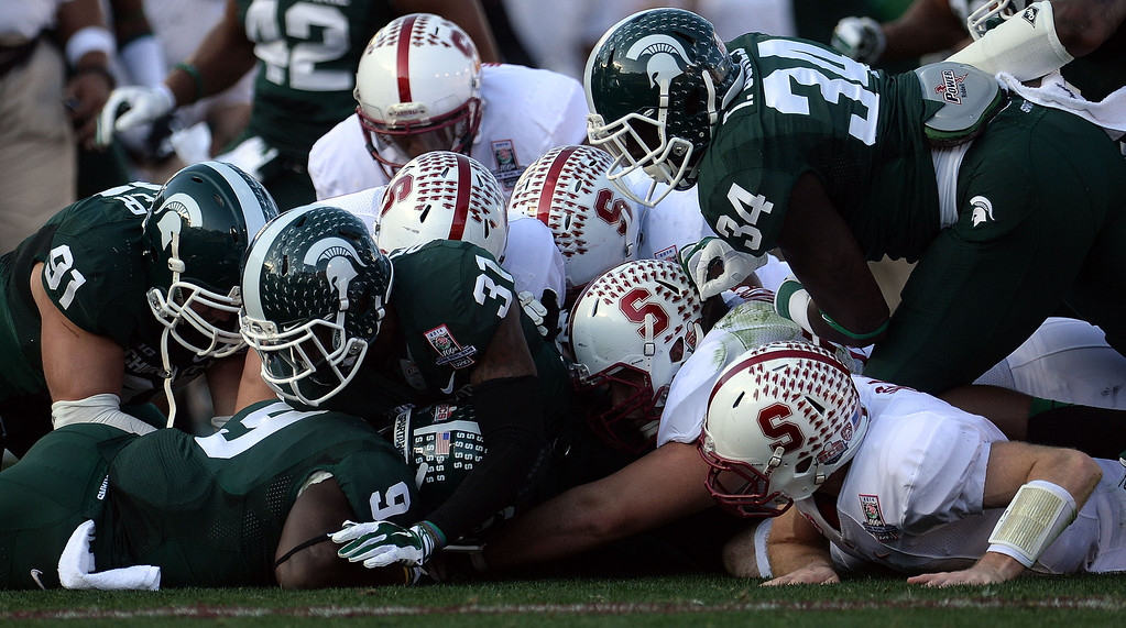 . Stanford recovers their own fumble in the first half of the 100th Rose bowl game against Michigan State in Pasadena, Calif., on Wednesday, Jan.1, 2014. 