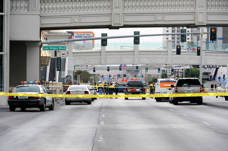 . Las Vegas Metro officers investigate the site of what is being described as a gun battle between shooters in vehicles along the Las Vegas Strip on February 21, 2013 in Las Vegas, Nevada. According to reports gunshots were fired between black SUV at a Maserati, causing the Maserati to crash into a taxi, that burst into flames. Five vehicles were involved in the subsequent crash with the Maserati driver and two people in the taxi being killed.  (Photo by David Becker/Getty Images)