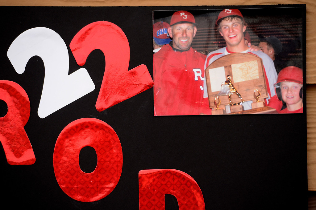 . PARKER, CO - APRIL 29: Regis Jesuit shortstop Brody Weiss\' poster board for senior day hangs on the concession stands during the team\'s final home game. Pictured with Weiss are his father, Walt, and brother, Brock. (Photo by AAron Ontiveroz/The Denver Post)