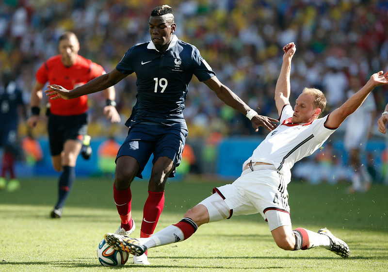 . Germany\'s defender Benedikt Hoewedes (R) tackles France\'s midfielder Paul Pogba during the quarter-final football match between France and Germany at the Maracana Stadium in Rio de Janeiro during the 2014 FIFA World Cup on July 4, 2014. (ADRIAN DENNIS/AFP/Getty Images)
