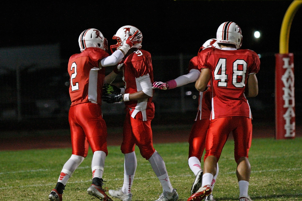 . Austin Manigo #9 of Lawndale is congratulated by teammates after scoring a touchdown against the defense of El Segundo in a Pioneer League matchup at Leuzinger High School on Friday, October 11, 2013 in Lawndale, Calif.  (Michael Yanow / For the Daily Breeze)
