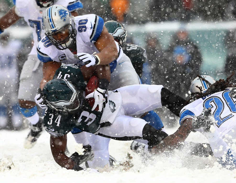 . Bryce Brown #34 of the Philadelphia Eagles is tackled by Ndamukong Suh #90 of the Detroit Lions on December 8, 2013 at Lincoln Financial Field in Philadelphia, Pennslyvania.  (Photo by Elsa/Getty Images)