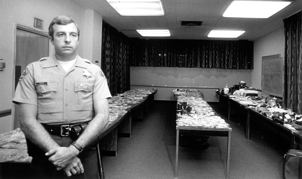 . Property believed stolen by the Night Stalker is guarded by Sheriff\'s Deputy Thomas Martin.  (Daily News file photo)