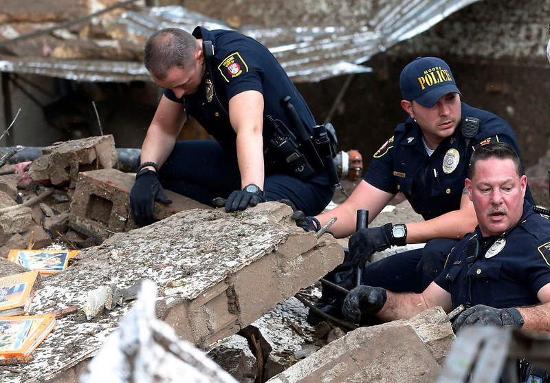 . Moore police dig through the rubble of the Plaza Towers Elementary School following a tornado in Moore, Okla., Monday, May 20, 2013. A tornado as much as a mile (1.6 kilometers) wide with winds up to 200 mph (320 kph) roared through the Oklahoma City suburbs Monday, flattening entire neighborhoods, setting buildings on fire and landing a direct blow on an elementary school. (AP Photo/Sue Ogrocki)