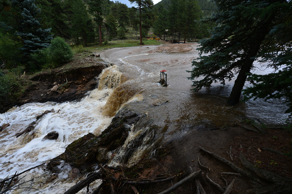 . Water streams out of Dorsey Lake on Saturday, Sept 14, 2013 after the dam was breached by flood waters. While the road in and the small pond were damaged, only minor water damage was reported at the YMCA of the Rockies. Walt Hester/Estes Park Trail-Gazette