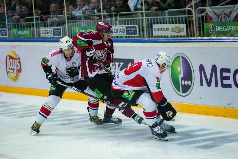 Kondratyev Maxim (63) un Vasilchenko Alexei (29) atņem ripu Dinamo Riga uzbrucējam Rustams Begovs (7)