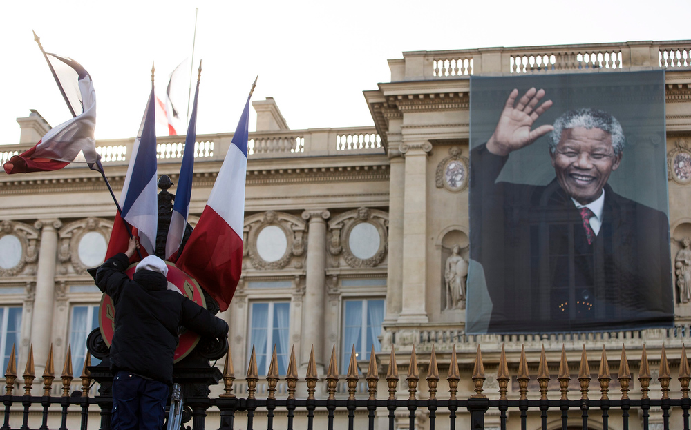 . Workers remove French flags from the front entrance of the Quai d\'Orsay foreign affairs ministry adorned by a giant portrait of the late Nelson Mandela, in Paris, France, 06 December 2013. Nobel Peace Prize winner Nelson Mandela died at age 95, in Johannesburg, South Africa, on 05 December 2013. A former lawyer, Mandela was the first black President of South Africa voted into power after the countries first free and fair democratic elections that witnessed  the end of the Apartheid system in 1994. Mandela was founding member of the ANC (African National Congress) and anti-apartheid activist who served 27 years in prison, spending many of these years on Robben Island. In South Africa, Mandela is often known as Tata Madiba, an honorary title adopted by elders of Mandela\'s clan. Mandela won the Nobel Peace Prize in 1993.  EPA/IAN LANGSDON