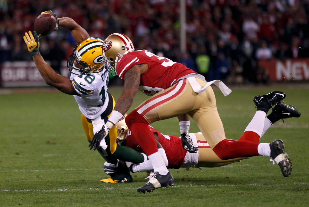 . Green Bay Packers Randall Cobb (L) makes a catch as he is tackled by San Francisco 49ers Dashon Goldson (R) and Tramaine Brock (C) during the third quarter in their NFL NFC Divisional play-off football game in San Francisco, California January 12, 2013.  REUTERS/Robert Galbraith