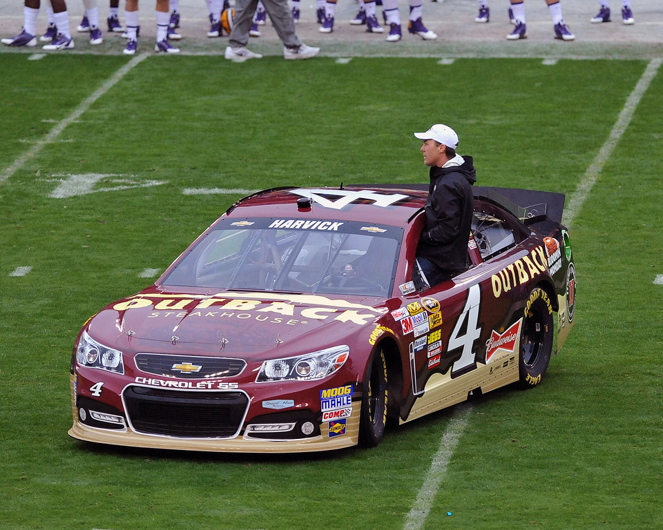 . NASCAR driver Kevin Harvick jumps from his car to toss the coin before play as the Iowa Hawkeyes take on the LSU Tigers January 1, 2014  in the Outback Bowl at Raymond James Stadium in Tampa, Florida.  (Photo by Al Messerschmidt/Getty Images)