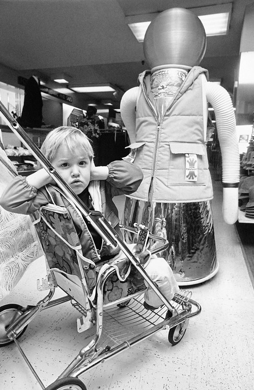 . Three-year-old Nikki Riehle holds her hands over her ears as she looks away from Sam Struggle Gear during a visit to a Cincinnati store, Oct. 27, 1977. The robot, which plays loud recordings from Star Wars, talks, blows a siren and sounds a horn, is the basic model of a highly technical device that has several applications. (AP Photo/Brian Horton)