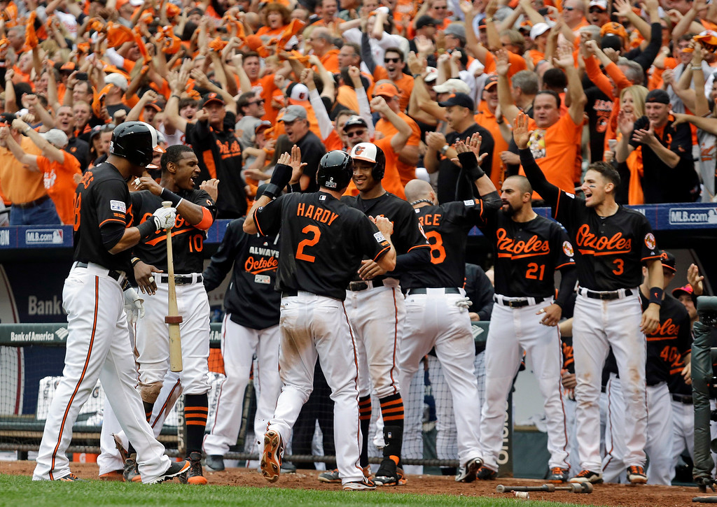 . Baltimore Orioles\' J.J. Hardy (2) celebrates with teammates after scoring the go-ahead run in the eighth inning of Game 2 in baseball\'s AL Division Series against the Detroit Tigers in Baltimore, Friday, Oct. 3, 2014. Baltimore won 7-6. (AP Photo/Patrick Semansky)