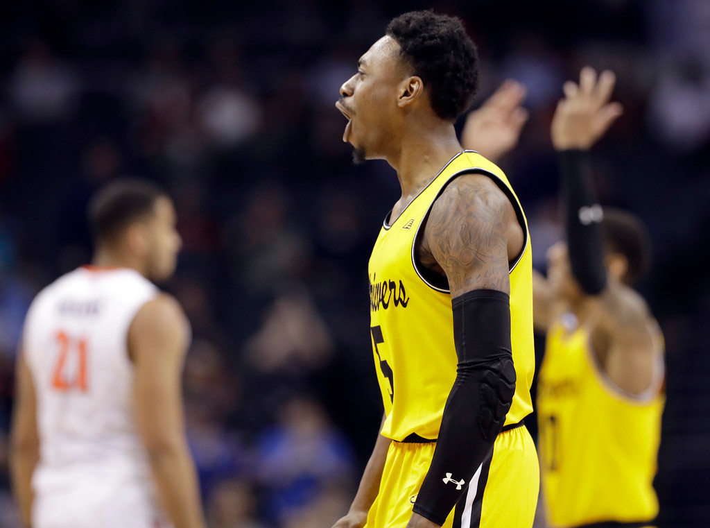 . UMBC\'s Jourdan Grant (5) celebrates after a basket against Virginia during the second half of a first-round game in the NCAA men\'s college basketball tournament in Charlotte, N.C., Friday, March 16, 2018. (AP Photo/Gerry Broome)