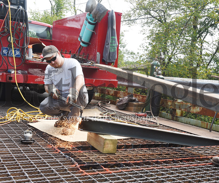 Harold Aughton/Butler Eagle: Hunter Bartolicius of the Butler County bridge crew cuts the edge of a replacement beam to fit on the Ash Stop Road bridge in Forward Twp.Monday, September 16, 2019.
